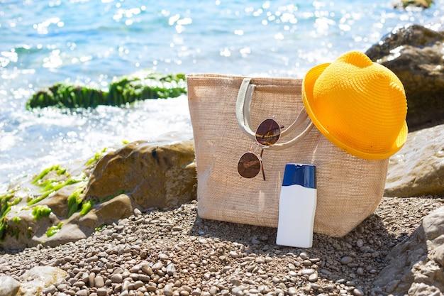 Strandtasche mit einer weißen tube sonnencreme an einem kieselstrand in der nähe des meeres. reise