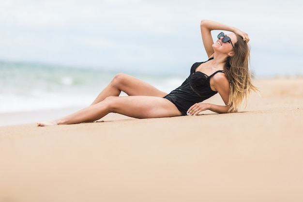 Strandurlaub bikini frau, die am strand nahe ozean entspannt.