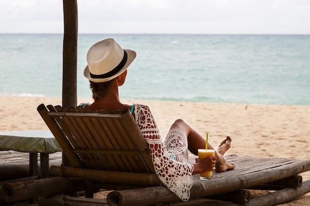Strandurlaub. dünne schönheit im sonnenhut, der auf ruhesessel liegt