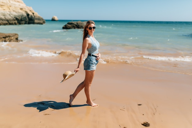 Strandurlaub. schöne frau im sonnenhut, die den perfekten sonnigen tag genießt, der auf dem strand geht. glück und glückseligkeit.