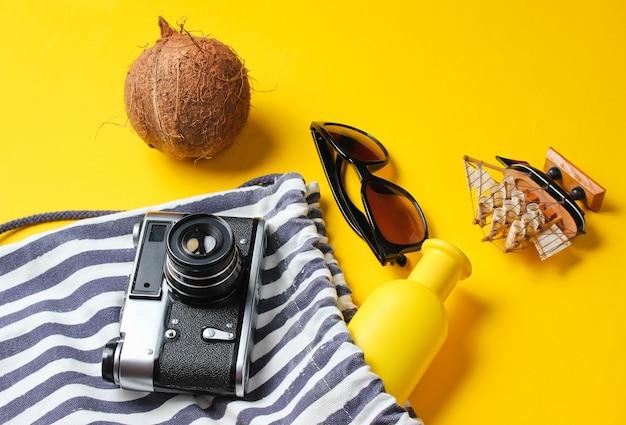 Strandurlaubszubehör auf gelbem grund. kreativer hintergrund des sommers.