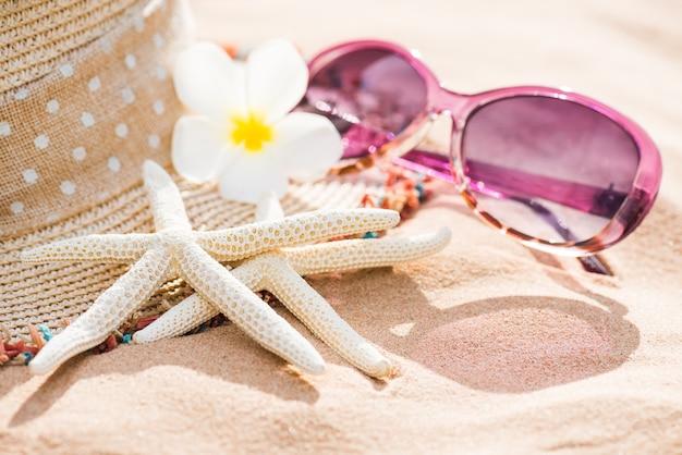 Strandzubehör auf hintergrund des sandigen strandes für sommer