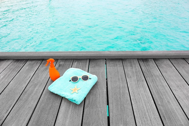 Strandzubehör auf holzponton im seebad. sommerferienkonzept