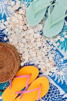 Strandzubehör auf sommertuch als hintergrund, reiseurlaubskonzept flach liegen