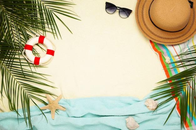 Strandzubehör mit palmblättern auf hellem hintergrund