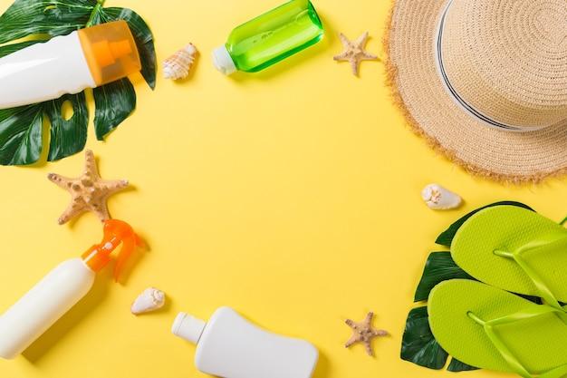 Strandzubehör mit strohhut, sonnencremeflasche und seastar auf gelber hintergrunddraufsicht mit kopienraum.