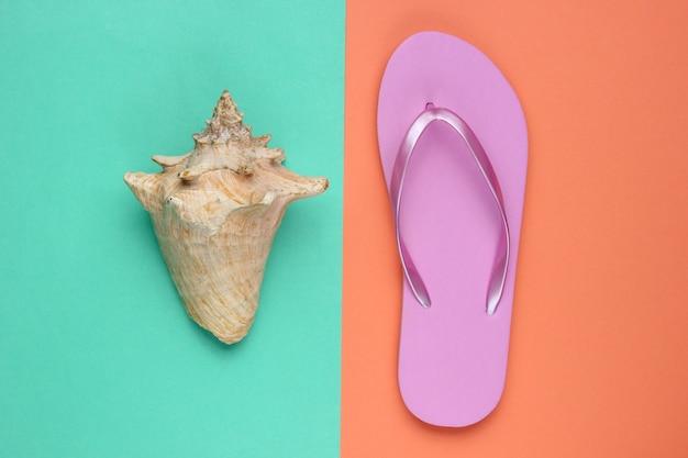 Strandzubehör. modische strandrosa flipflops, muschel auf korallenblauem papierhintergrund. flach liegen. draufsicht