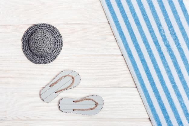 Strandzubehör. sommerschuhe - flip-flops, baumwolltuch mit blauen streifen, hut von der sonne