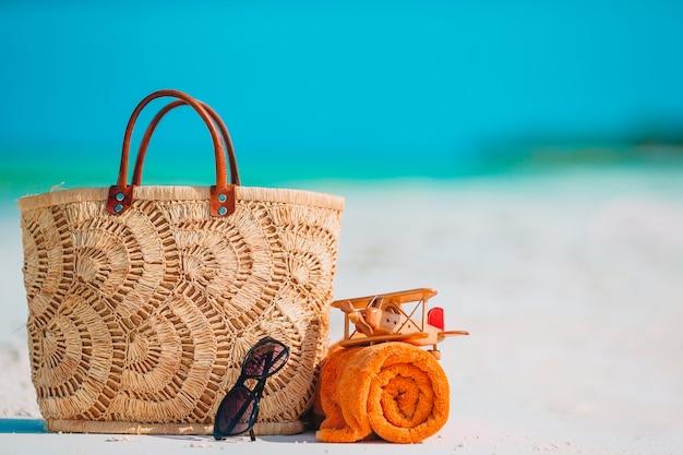 Strandzubehör - tasche, strohhut, sonnenbrille am weißen strand