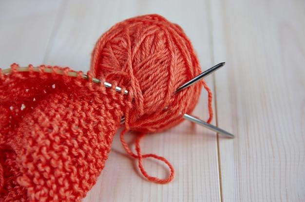 Strang aus wollrotem faden, mit stricknadeln zum handstricken auf einem holztisch
