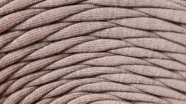 Strang der grauen strickgarnnahaufnahme. makrophotographiehintergrundbeschaffenheitsmusterwebartfaser-textilgewebe. gewebestreifen sind auf einer rolle verwoben.