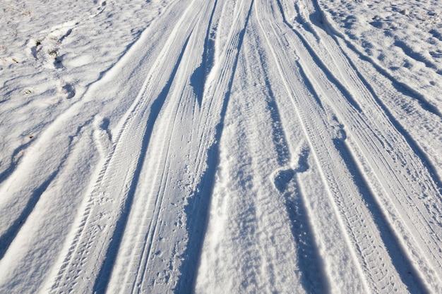 Straße auf dem land, auf dem feld gelegen. winterzeit des jahres, auf der straße liegt schnee und man kann spurrillen auf der oberfläche sehen. nahaufnahmefoto