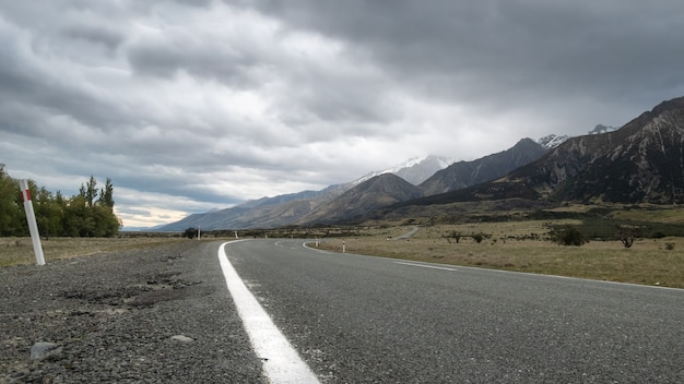Straße, die in richtung berge führt, mit bewölktem himmel, niedrige perspektive, aufgenommen in neuseeland