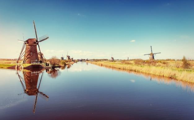 Straße, die vom kanal zu den niederländischen windmühlen führt