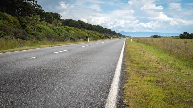 Straße, die während des sonnigen tages zum geraden horizont der distanz führt, westküstenregion von neuseeland