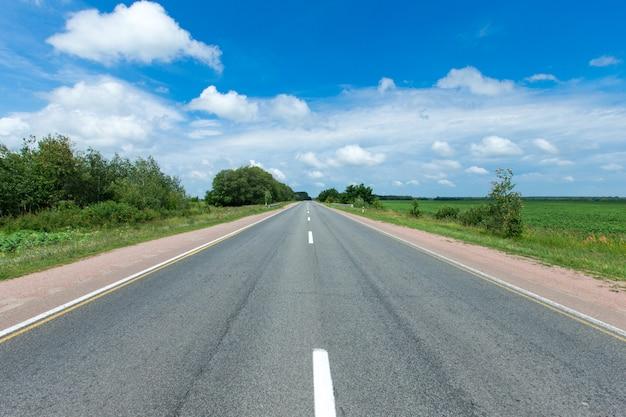 Straße durch das grüne feld und die wolken auf blauem himmel am sommertag