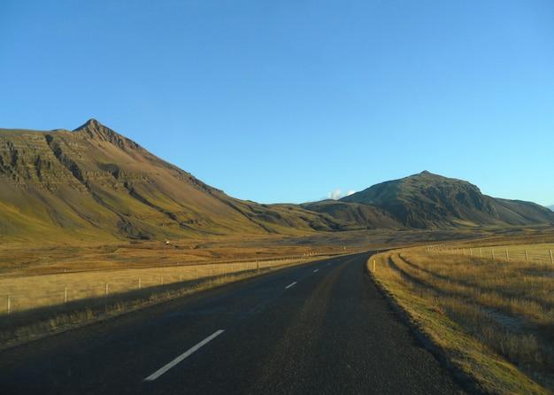 Straße entlang dem gebirgszug an einem sonnigen nachmittag, island