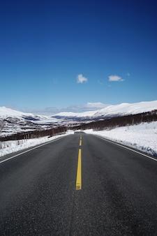 Straße führt zu schönen schneebedeckten bergen