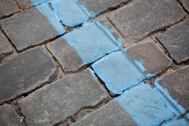 Straße gepflastert mit granitsteinen mit blauer markierungslinie. nahaufnahme