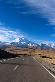 Straße in den bergen, kaukasus, sonniger tag elbrus, bewölkt