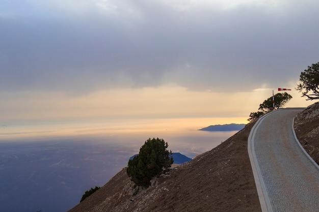 Straße in den bergen mit gelbem sonnenuntergang und dem meer