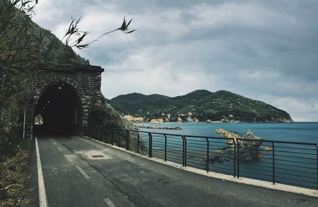 Straße in richtung eines tunnels im berg nahe einem meer mit bergen