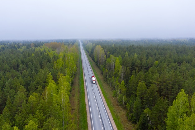 Straße mit autos im wald zwischen grünen bäumen, luftaufnahme von der drohne