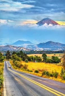 Straße mit dem vulkan popocatepetl im hintergrund, mexiko