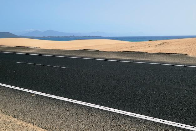 Straße mit schöner aussicht auf den strand und überquert die dünen