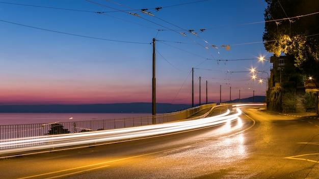 Straße neben einem ozean in montreux, schweiz während des sonnenuntergangs mit lichtspuren