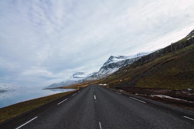 Straße, umgeben von fluss und hügeln, bedeckt mit schnee und gras unter einem bewölkten himmel in island