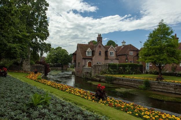 Straße, umgeben von gebäuden und gärten nach dem regen in canterbury im vereinigten königreich