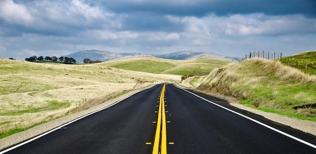 Straße umgeben von grünen landschaften unter dem bewölkten himmel