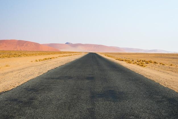 Straße, welche die namibische wüste kreuzt