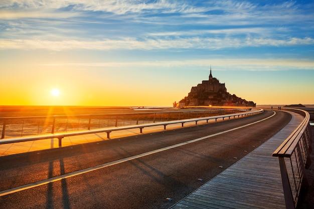 Straße zum mont saint michel bei sonnenuntergang, normandie. frankreich.