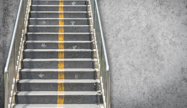 Straßen-gehweg-überführungstreppe mit zementhintergrund für plakat und fahne