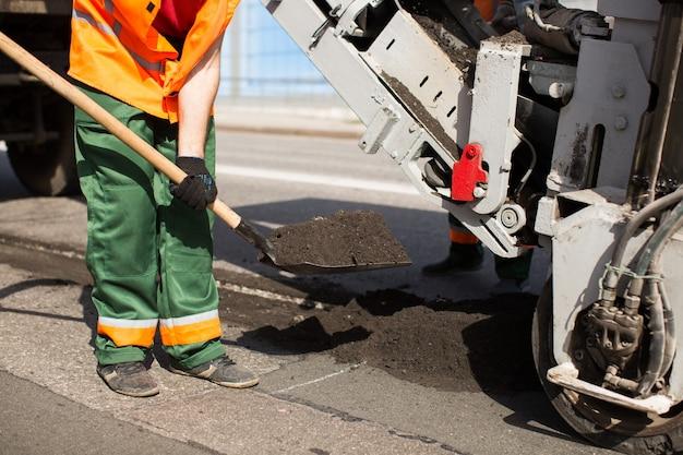 Straßenarbeiter reparieren arbeiten. arbeitsschlaf schaufelt das material in die maschine.