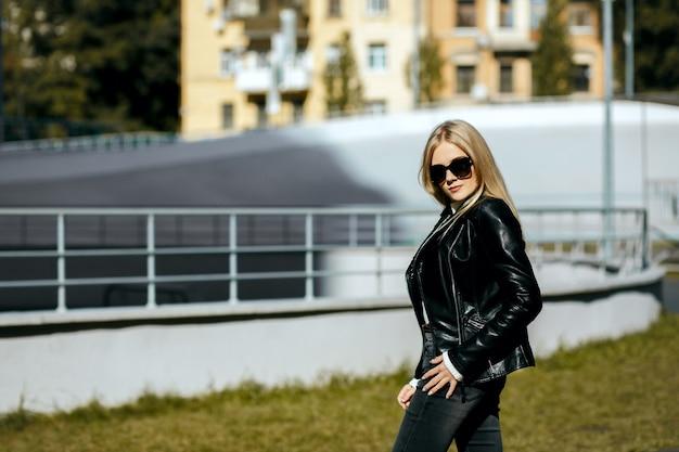 Straßenaufnahme eines wunderschönen blonden models mit lederjacke und brille. platz für text