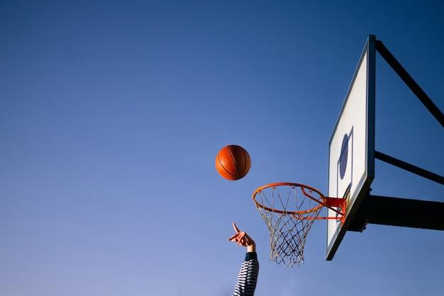 Straßenbasketballballspieler, der ball in den reifen wirft