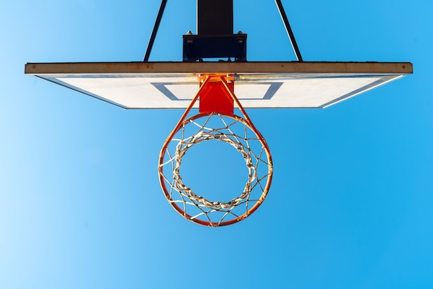 Straßenbasketballkorb an einem sonnigen tag mit blauem himmel in der oberfläche.