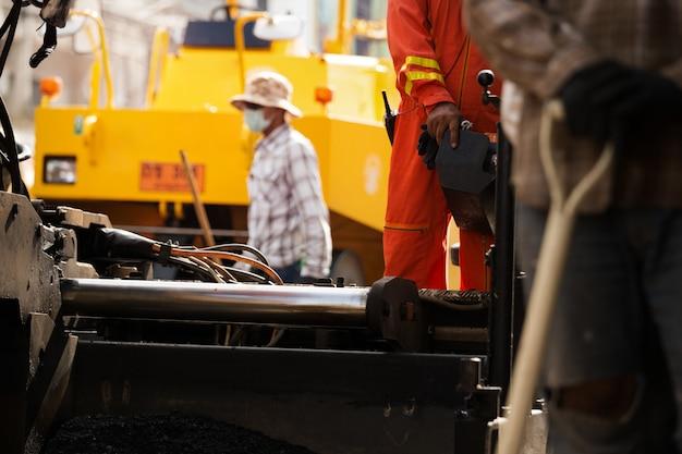 Straßenbauarbeiter, die asphaltstraße reparieren.