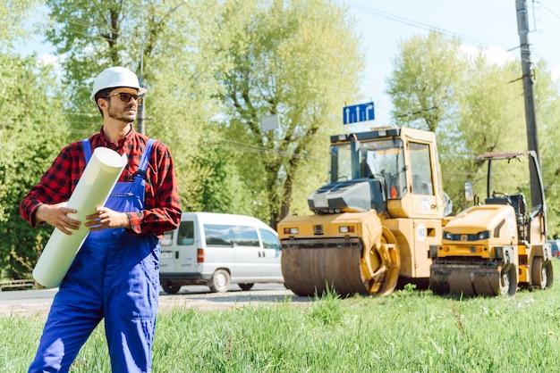 Straßenbauarbeiter in der nähe von asphaltfertiger. straßenreparatur. straßenarbeiter in der nähe der eisbahn.