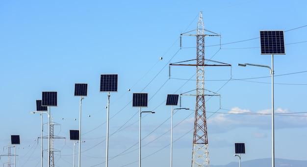 Straßenbeleuchtung funktioniert aus sonnenkollektoren. vor dem stromübertragungsmast. konzeptionelle