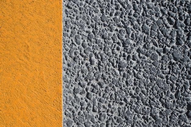 Straßenbeschaffenheit mit gelber linie. dunkler körniger asphalt der straße und helle bordsteinmarkierungen. strukturierter hintergrund mit textfreiraum