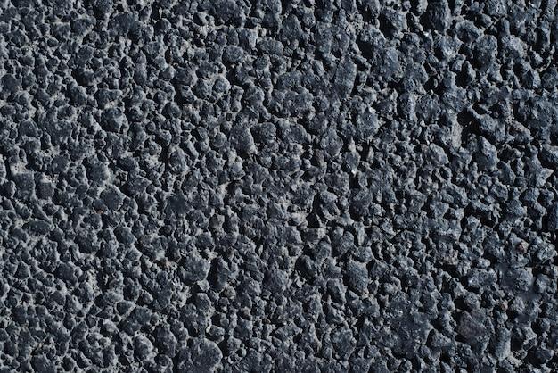 Straßenbeschaffenheit. nahaufnahme einer dunklen asphaltstraße im freien, draufsicht. rauer körniger oberflächenhintergrund.
