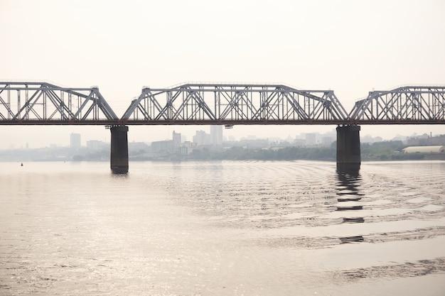 Straßenbrücke über einen breiten fluss und die silhouette einer fernen stadt dahinter im morgendunst