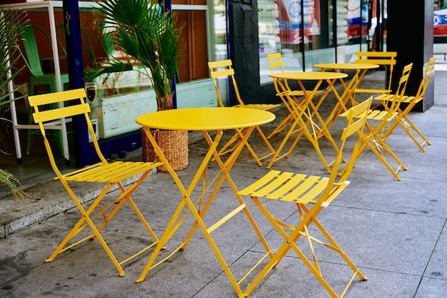 Straßencafé-interieur mit gelbem tisch und stühlen