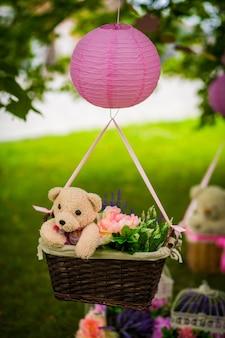 Straßendekorationen für eine kinderparty. ein korb mit einem teddybär in einem luftballon in einem grünen park.