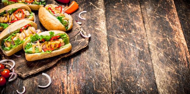 Straßenessen. hot dogs mit kräutern, gemüse und heißem senf. auf hölzernem hintergrund.