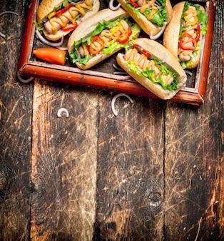 Straßenessen. hot dogs mit senf, scharfer soße, zwiebel und gemüse auf holztisch.